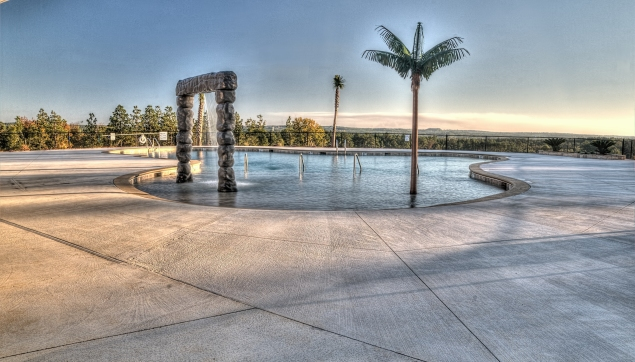 An image of the pool with plam tree and sunset at Greggs Mill.