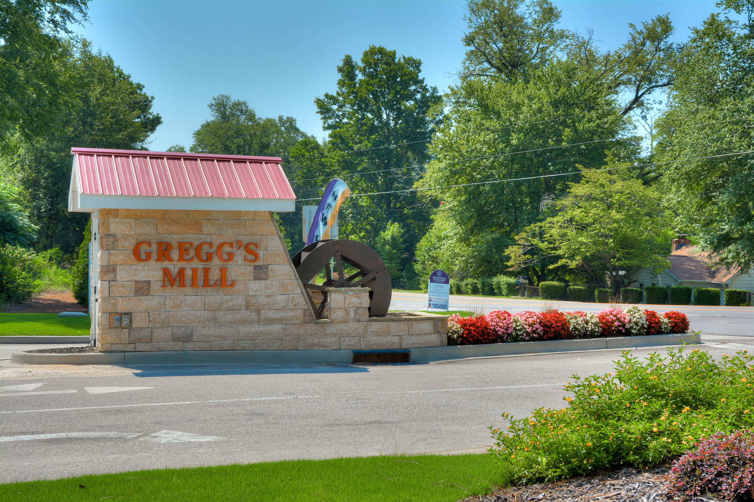 An image of Greggs Mill entrance with flowers.
