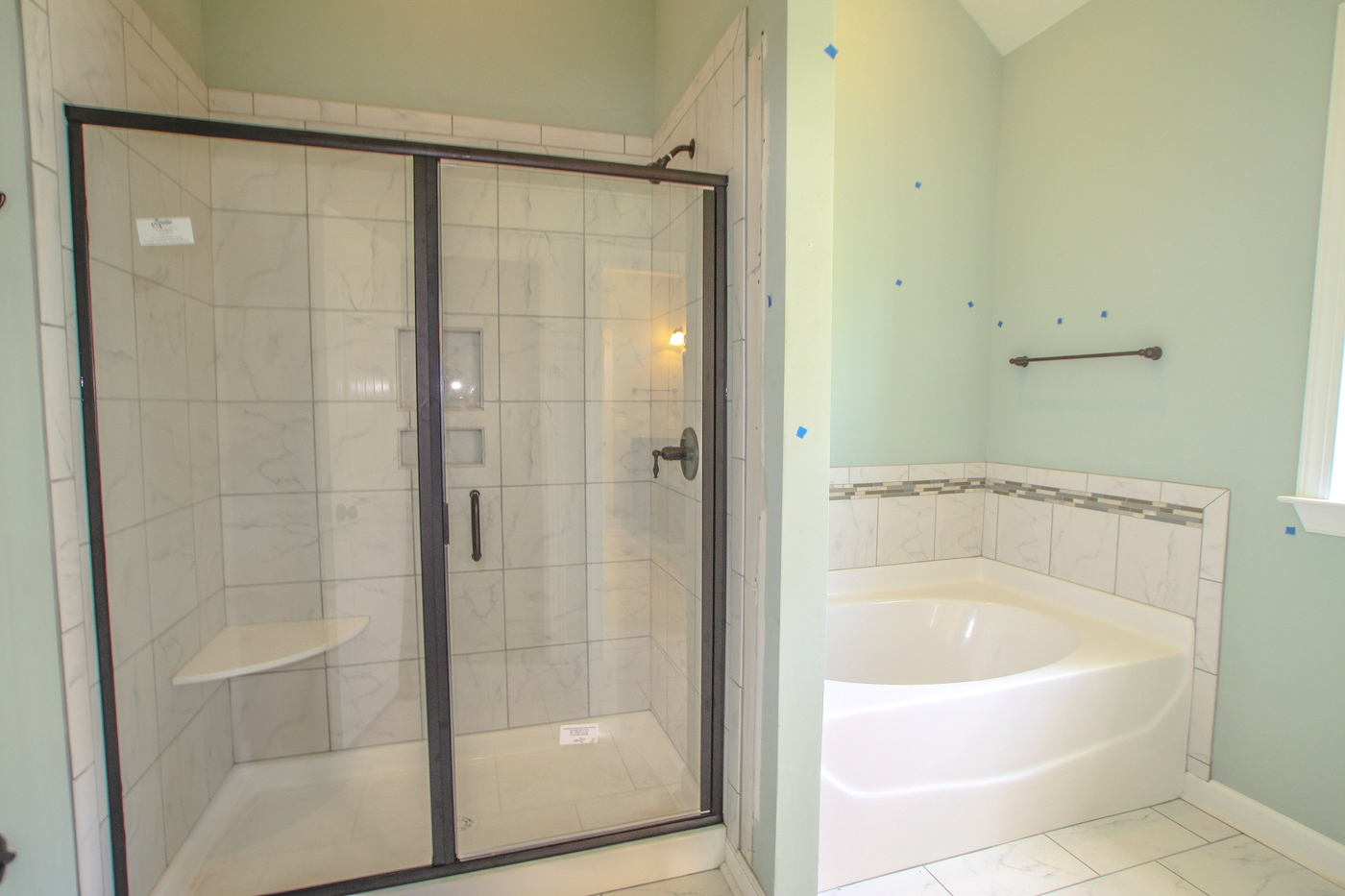 Am image of a green bathroom with shower and bath.